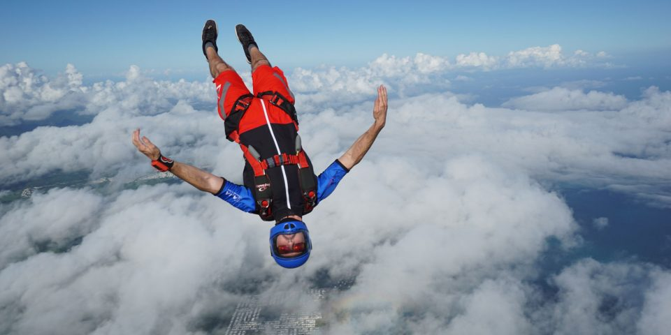 Fun jumper wearing red, blue and black jump suit head down during free fall.