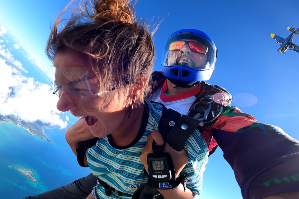 Female tandem skydiver smiles during freefall looking down at the beautiful ocean views