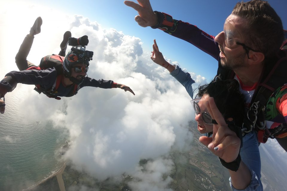 Tandem skydiver throws up peace signs during freefall looking out over the ocean