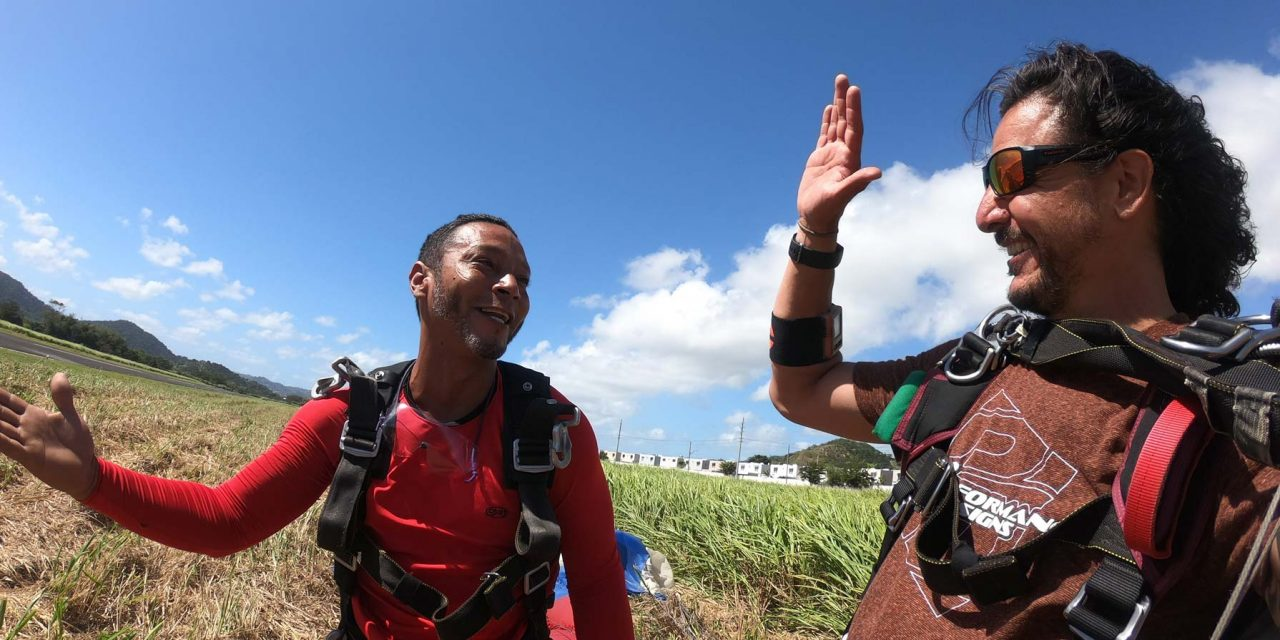 Tandem skydiver and coach smiling and high-fiving one another after an awesome skydive at La Zona Puerto Rico Skydiving