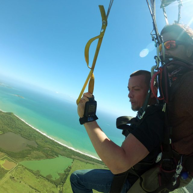 Male tandem skydiver looks out at the beautiful ocean during the canopy portion of his skydive