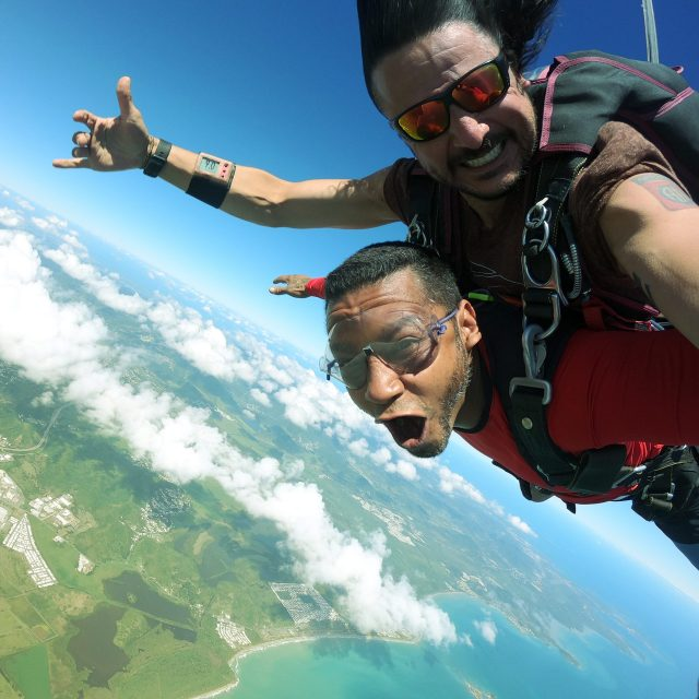 Man wearing red shirt skydives over the beautiful east coast ocean in Puerto Rico
