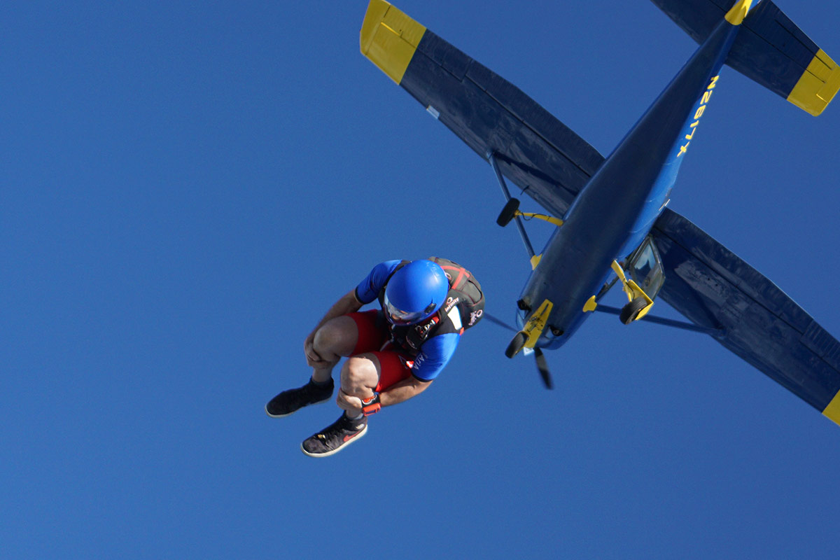 Experienced jumper wearing blue helmet takes the leap out of the La Zona Puerto Rico Skydiving aircraft
