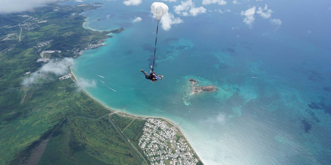 Aerial view of tandem skydivers over Puerto Rico's east coast