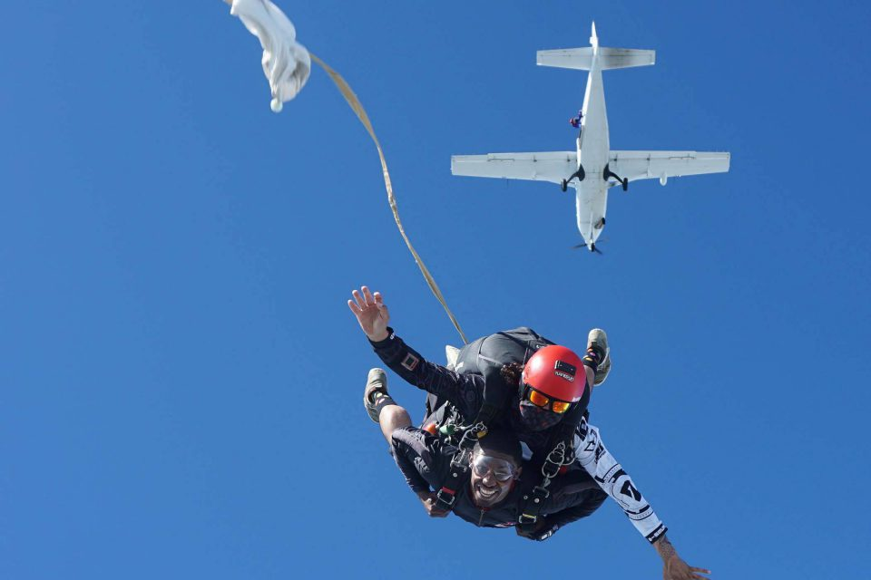 La Zona Puerto Rico Skydiving tandem coach wearing a red helmet and mask have arms out during free fall portion of skydive