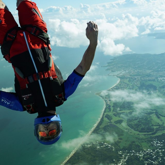 Experienced jumper wearing blue helmet skydives over Puerto Rico's lush El Yunque Rain Forest & stunning East Coast