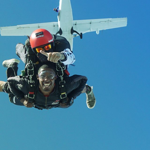 Tandem skydiving coach gives a thumbs after leaping from the La Zona Puerto Rico Skydiving aircraft